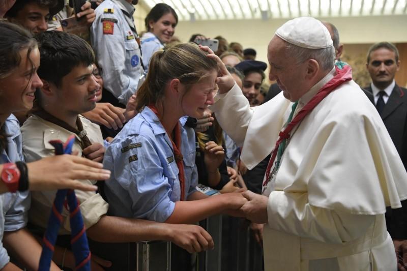 Francisco, con el pañuelo scout, bendice a una joven