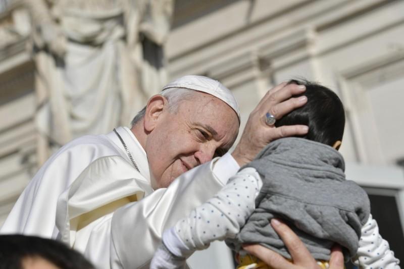 Francisco besa a un niño