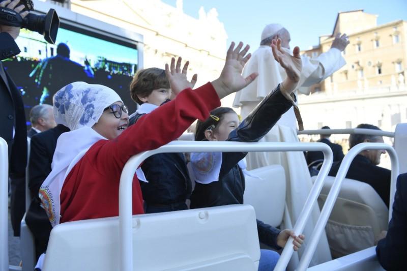 Los niños y el Papa saludan desde el jeep